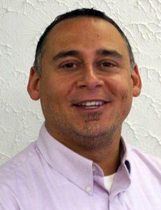 Smiling man wearing lavender oxford shirt